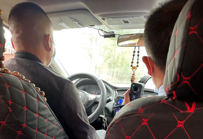 強盗事件の容疑者とされるタクシー運転手(左)と、記者を動画で撮影し続ける警察官(右側)=9月、青海省海東市(撮影・坂本信博)