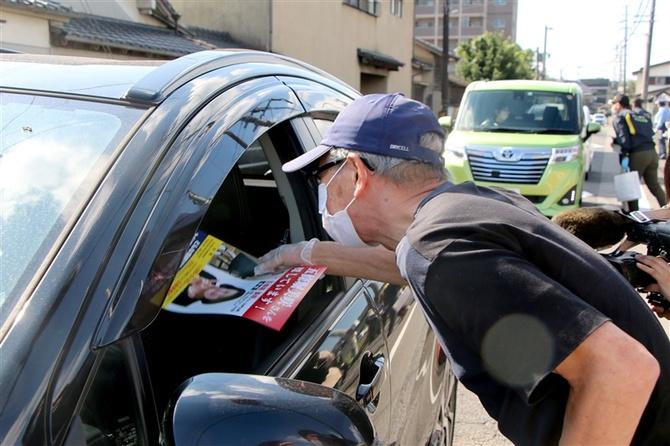 五條堀美咲さんが暮らしたアパート付近で情報提供のチラシを配る父親=24日午前、大分市横尾