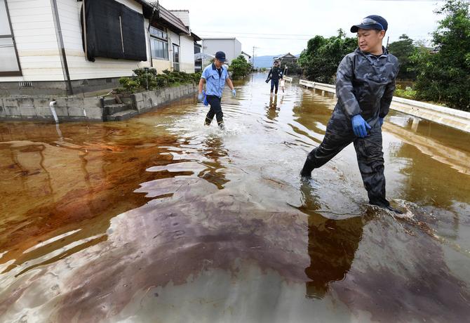 住宅地に浮遊する大量の油からは異臭が漂っていた=30日午前10時20分ごろ、佐賀県大町町