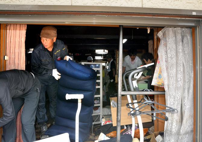 浸水した住宅から家具を運び出すボランティアたち=31日午前10時20分 ...