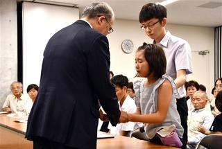 中村法道知事(左)に手紙を渡す、石木ダム予定地に暮らす女児と父親=19日午前10時半ごろ、長崎県庁