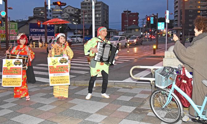 JR新飯塚駅前で配車アプリをPRするアダチ宣伝社