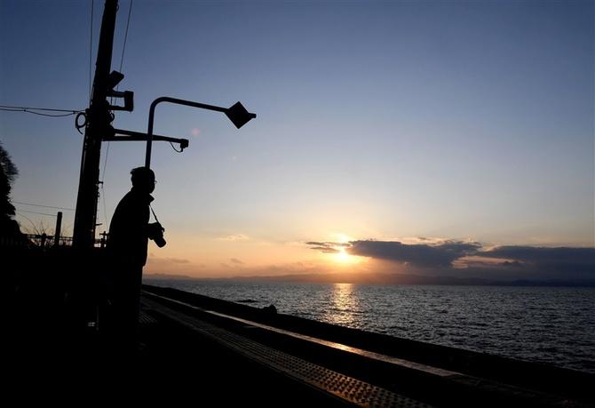 カメラを手にした男性が沈むゆく夕日に狙いを定めていた
