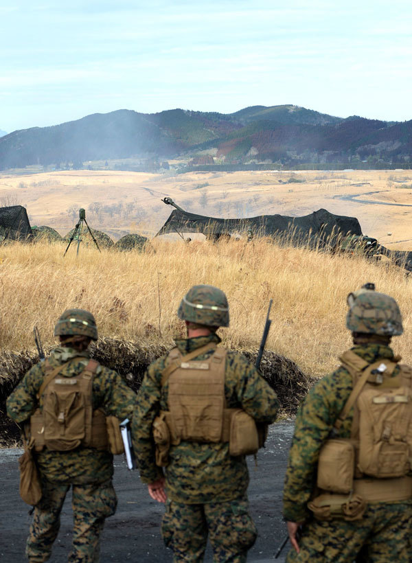報道陣に公開された、りゅう弾砲の訓練。手前は、訓練を見守る米海兵隊=14日午前10時51分、大分県玖珠町(撮影・宮下雅太郎)