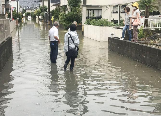 冠水した道路を心配そうに見つめる住民たち=27日午前9時すぎ、福岡県久留米市梅満町