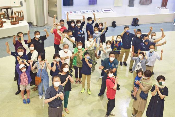 愛媛県松山市のイベントで三つの輪のマークを作るシトラスリボンプロジェクトのメンバー(甲斐朋香さん提供)