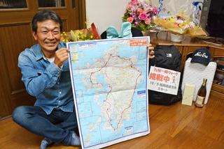 九州一周のコースを記した地図を持ち笑顔を見せる石田博道さん