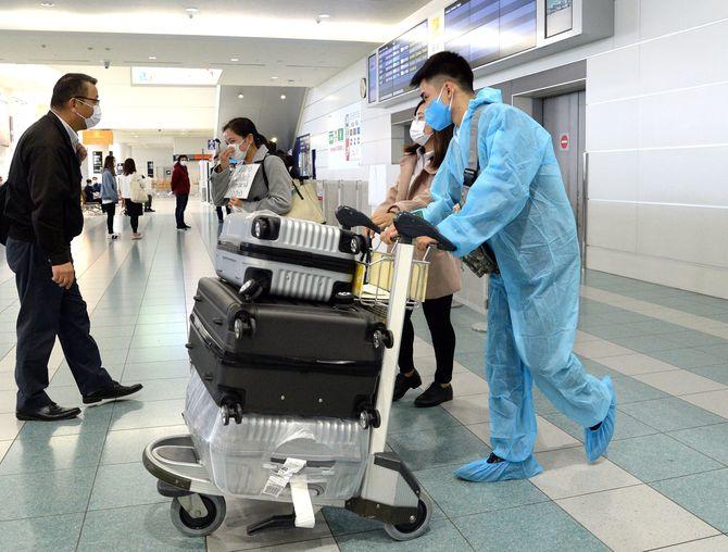 感染対策を意識した格好で、韓国・仁川から福岡空港に到着した乗客=23日午前11時21分、福岡市博多区(撮影・帖地洸平)