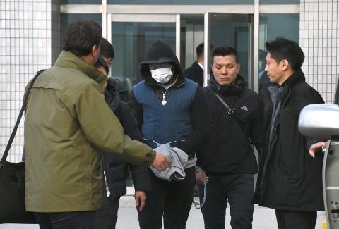 関東から福岡空港に移送された容疑者の男(中央のマスク姿)=22日 ...