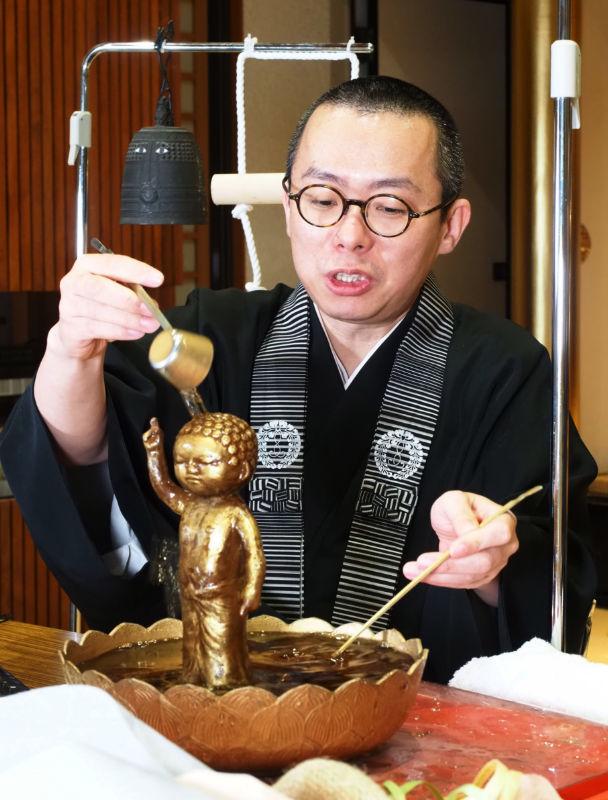 リツイートした人に代わって仏像に甘茶を掛ける松崎智海さん