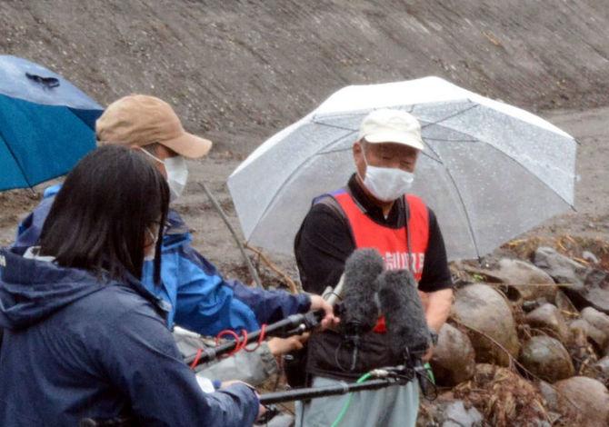 石木川沿いの工事現場で報道陣の取材に応じる住民たち
